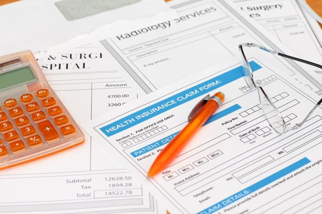 Surgery bills with health insurance claim calculator and pen - Medical Provider filing a lien instead of submitting bills to insurance